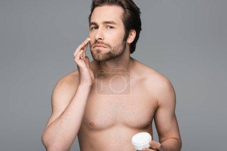 hombre sin camisa aplicando crema hidratante para la cara aislada en gris