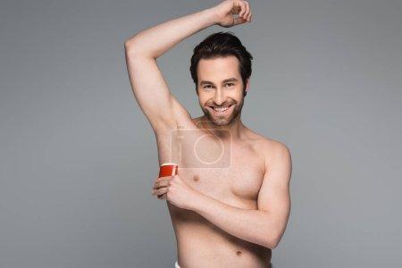 Photo pour Heureux homme torse nu appliquant déodorant bâton solide isolé sur gris - image libre de droit