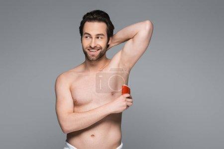Photo pour Homme torse nu gai appliquant déodorant bâton solide isolé sur gris - image libre de droit