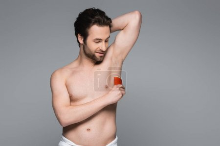 smiling shirtless man applying solid stick deodorant isolated on grey