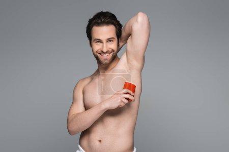 joyful shirtless man applying solid stick deodorant isolated on grey
