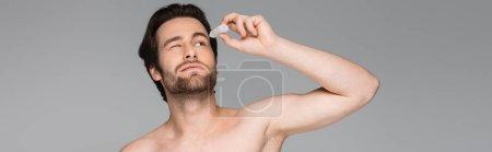 Hemdloser Mann mit geschlossenen Augen, der Augentropfen isoliert auf Grau aufträgt, Banner