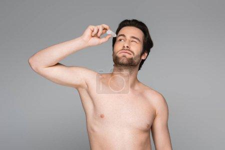 Hemdloser Mann mit geschlossenen Augen, der Augentropfen isoliert auf grau aufträgt