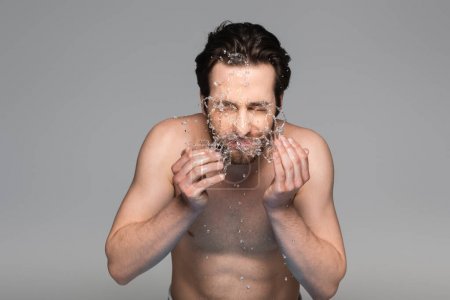 young bearded man with closed eyes washing face isolated on grey