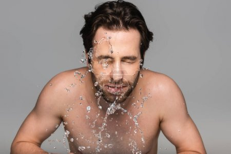 bearded man with closed eyes washing face with clear water isolated on grey