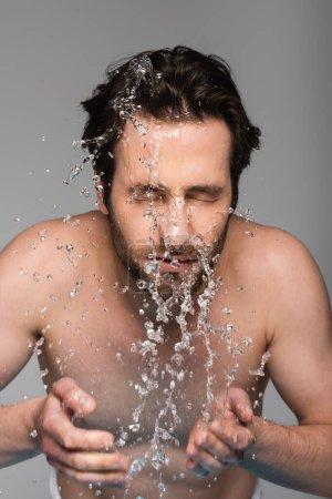 bearded man with closed eyes washing face isolated on grey