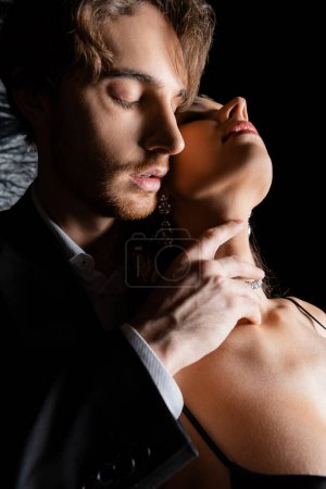seductive man holding hand on neck of sensual woman on black background