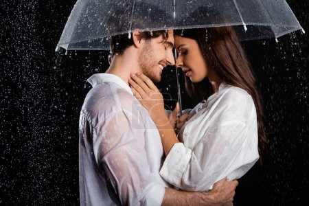 romantic young adult couple standing in rain with umbrella and hugging on black background