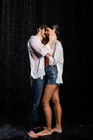 romantic young adult wet couple standing in rain and sensually hugging with hands on black background