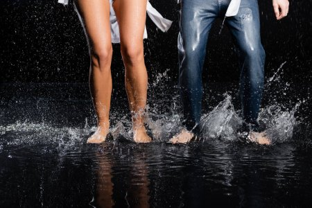 Photo for Partial view of male and female barefoot legs in water splashes on black background - Royalty Free Image