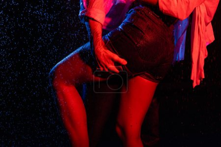 Photo for Cropped view of wet sexy man holding female buttocks in water drops, toned in red and blue on black background - Royalty Free Image