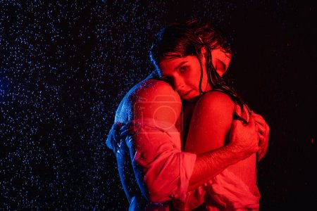 Photo for Red and blue colors filters picture of wet passionate romantic couple gently hugging in water drops on black background - Royalty Free Image
