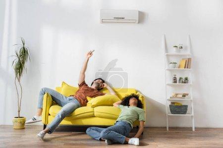 Photo pour Jeune homme tenant télécommande près du climatiseur tout en souffrant de chaleur avec une petite amie afro-américaine - image libre de droit