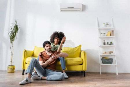 displeased interracial couple looking at remote controller while sitting on couch near air conditioner