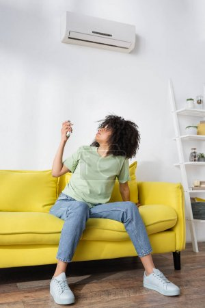 Photo for Disappointed african american woman holding remote controller while sitting on yellow couch and suffering from heat - Royalty Free Image