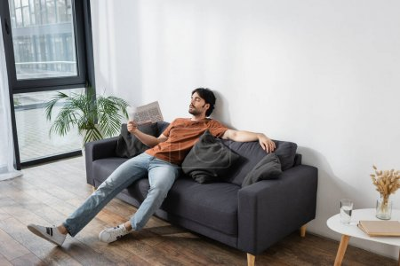 Photo for Man waving with newspaper while lying on gray sofa and suffering from heat - Royalty Free Image