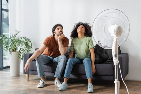 cheerful interracial man and woman sitting on couch near blurred electric fan in living room
