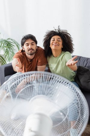 Photo for Happy interracial couple sitting on couch with outstretched hands near blurred electric fan in living room - Royalty Free Image