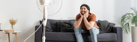 Photo for Happy bearded man sitting on couch near blurred electric fan, banner - Royalty Free Image