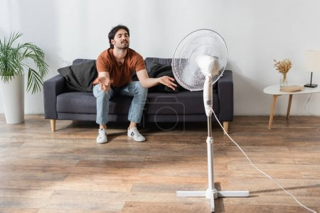 Photo for Pleased and bearded man sitting on couch near blurred electric fan - Royalty Free Image