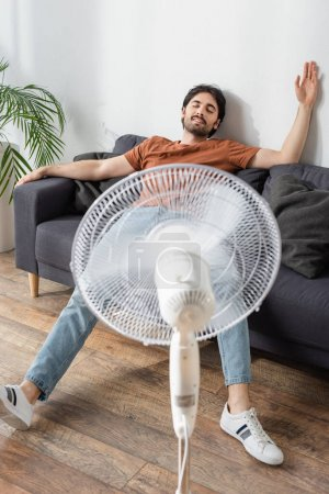pleased man sitting on couch near blurred electric fan