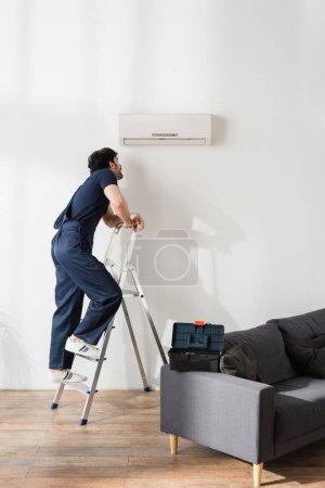 Photo pour Homme à tout faire barbu en salopette debout sur l'échelle et regardant climatiseur cassé - image libre de droit