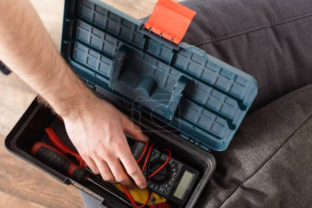 partial view of handyman taking digital multimeter from toolbox