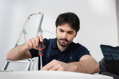 bearded handyman in overalls holding screwdriver while fixing broken air conditioner