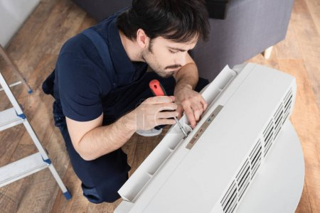 high angle view of bearded handyman holding screwdriver while fixing broken air conditioner