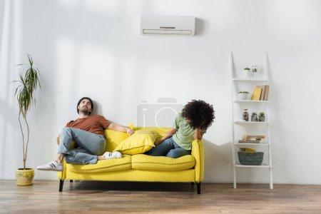 Photo pour Épuisé interracial couple assis sur canapé et souffrant de chaleur en été - image libre de droit