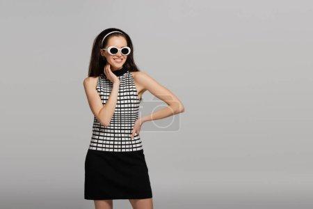 Photo pour Jeune modèle tendance en lunettes de soleil, bandeau et tenue rétro souriant isolé sur gris - image libre de droit