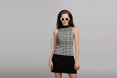 Photo pour Jeune modèle tendance en lunettes de soleil, bandeau et tenue rétro isolé sur gris - image libre de droit
