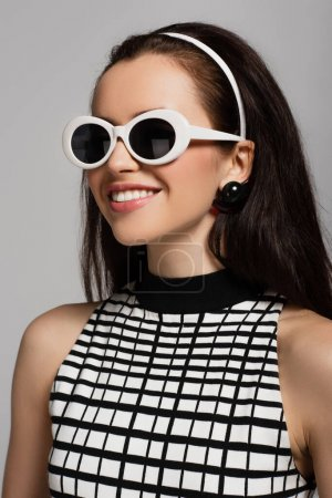 Photo for Trendy young model in sunglasses and headband smiling isolated on grey - Royalty Free Image
