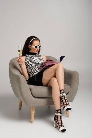 Photo pour Modèle brune dans des lunettes de soleil rétro lecture magazine et tenant un verre de champagne tout en étant assis sur un fauteuil sur gris - image libre de droit