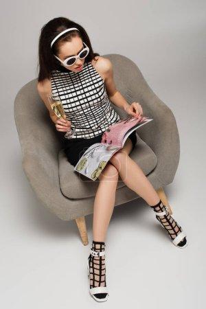 Photo pour Vue aérienne de la jeune femme en lunettes de soleil rétro lisant le magazine et tenant un verre de champagne assis sur un fauteuil gris - image libre de droit