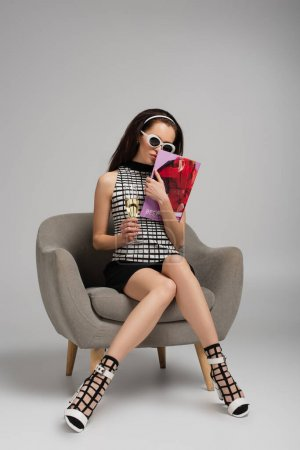 young woman in retro sunglasses holding magazine and glass of champagne while sitting on armchair on grey
