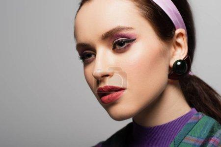 Photo pour Jeune femme en violet bandeau et boucle d'oreille regardant loin isolé sur gris - image libre de droit