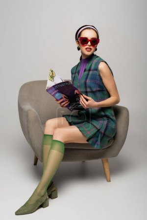 young woman in retro sunglasses holding magazine while sitting in armchair on grey