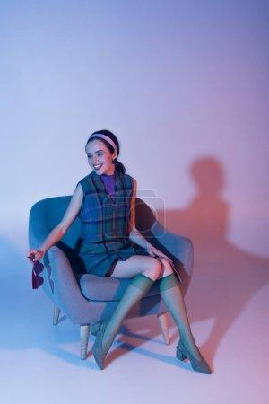 Photo pour Femme souriante tenant des lunettes de soleil et un magazine assis dans un fauteuil sur violet - image libre de droit
