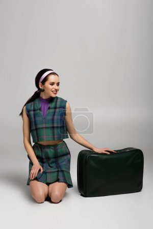 Photo for Cheerful woman in retro outfit sitting near green baggage on grey - Royalty Free Image