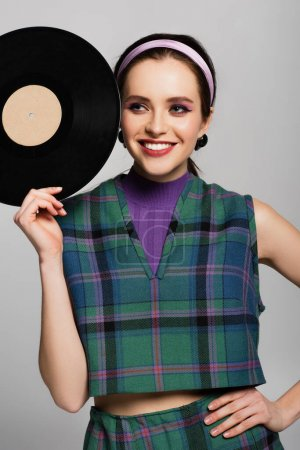 smiling woman in retro outfit holding retro vinyl disc isolated on grey