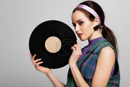 Photo for Pretty young woman in headband holding retro vinyl disc isolated on grey - Royalty Free Image