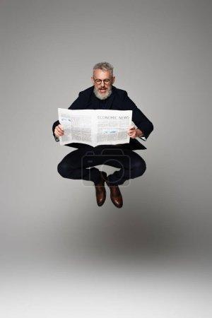 Photo pour Pleine longueur de l'homme d'âge moyen dans des lunettes et costume lecture nouvelles économiques tout en lévitant sur gris - image libre de droit