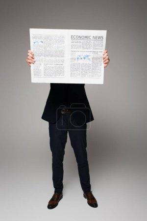 Photo pour Toute la longueur de l'homme couvrant le visage tout en lisant les nouvelles économiques sur gris - image libre de droit