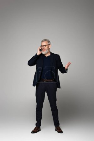 full length of happy man with grey hair talking on smartphone while gesturing on grey