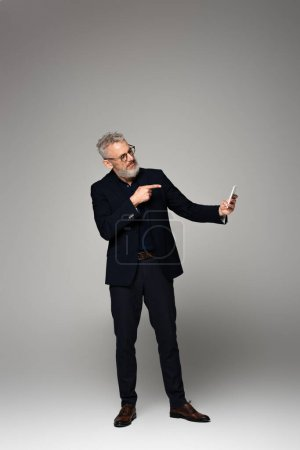 Photo for Full length of businessman with grey hair pointing with finger while taking selfie on grey - Royalty Free Image