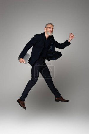 full length of happy man with grey hair holding laptop while levitating on grey