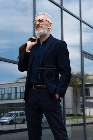 Photo for Tattooed mature man with grey hair holding leather bag while standing outside - Royalty Free Image