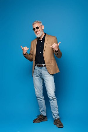 Photo for Full length of cheerful middle aged man in sunglasses showing call me gesture on blue - Royalty Free Image