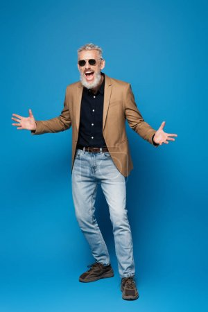 full length of excited middle aged man in sunglasses gesturing on blue